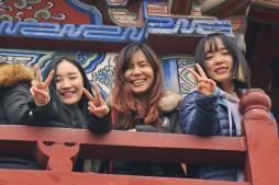 סטודנטית סינית (מימין), תאילנדית (במרכז) וקוריאנית (מימין) משקיפות מהמגדל בהיכל הממשלה בקאי-פנג